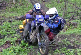 Off-road people help each other on a hill climb