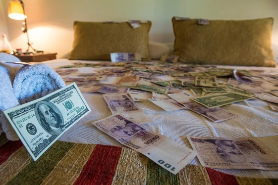 Cash on the bed in different currencies.