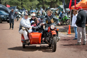 Nicole Espinosa riding a sidecar around motorcycle village at overland expo 2015