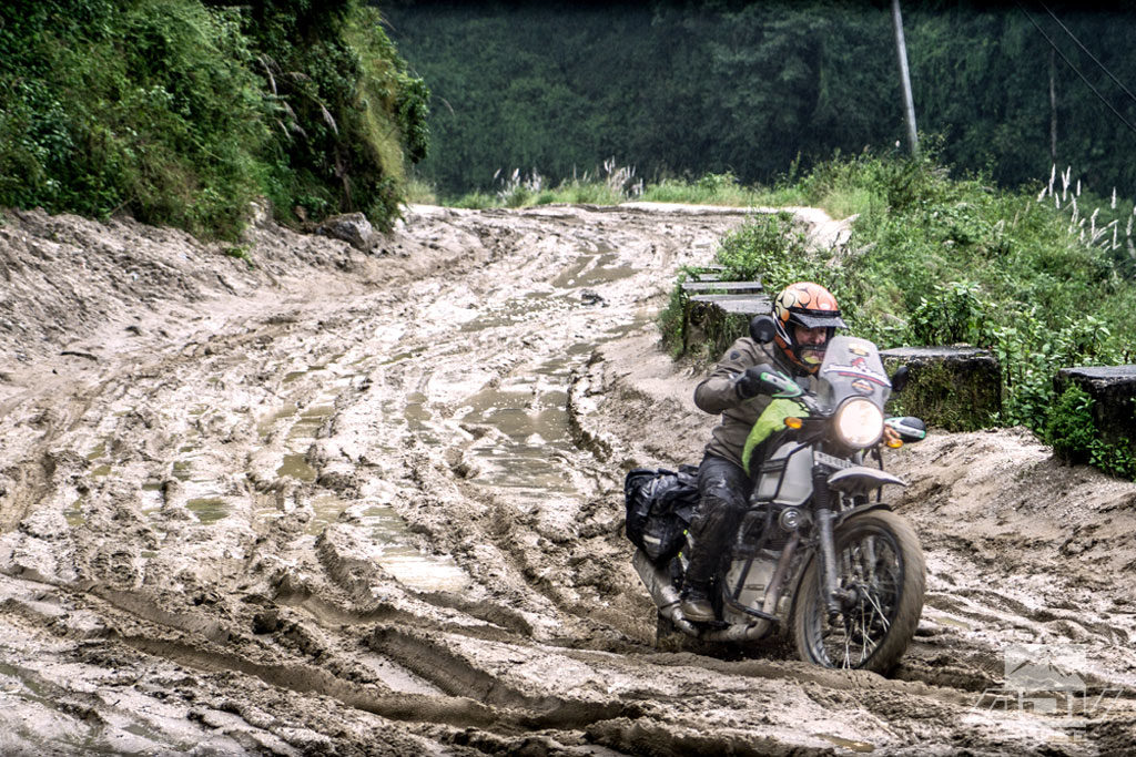 Negotiating deep mud on a motorcycle expedition to Everest